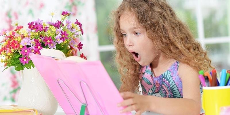 девочка читает книгу в слух