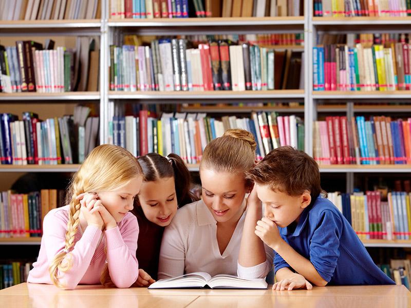 дети смотрят книгу вместе с мамой